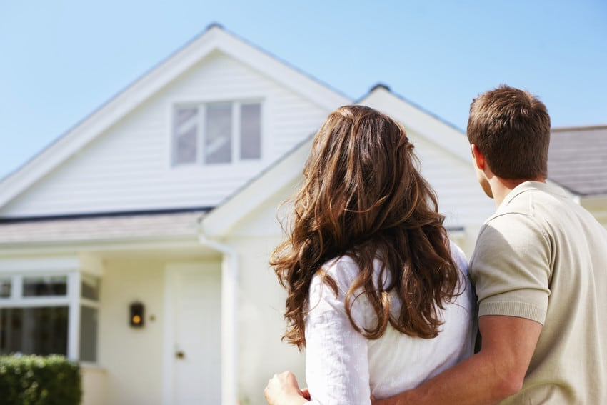 Two young people standing close together and looking at the single-story home they just bought.