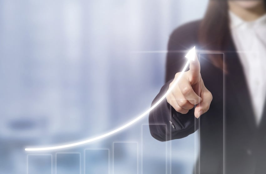 A woman gesturing to a graph that shows a value steadily increasing over the years.